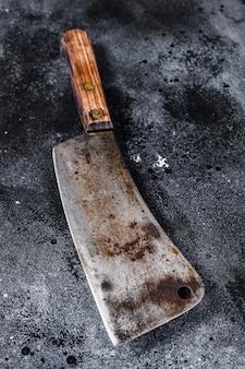 Tasak do mięsa na starej porysowanej czarnej teksturze. widok z góry
