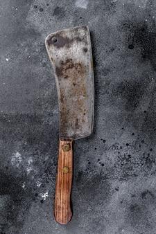 Tasak do mięsa na starej porysowanej czarnej teksturze.