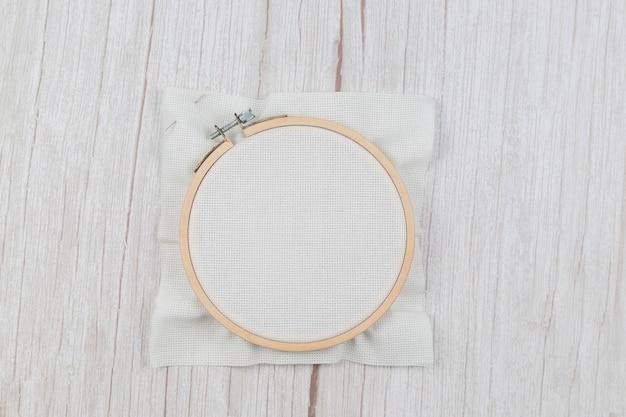 Taśma do haftu krzyżykowego z rozciągniętego płótna, pusta dla projektanta, na drewnianym tle