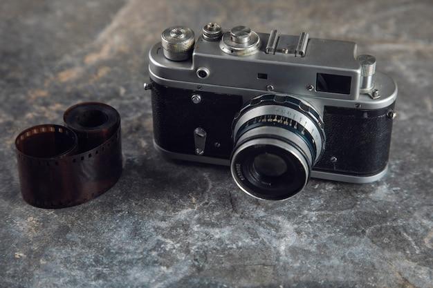 Taśma fotograficzna i zabytkowy aparat na stole