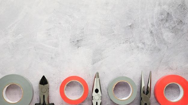 Taśma izolacyjna i szczypce ułożone w rzędzie na betonowej podłodze z białego cementu