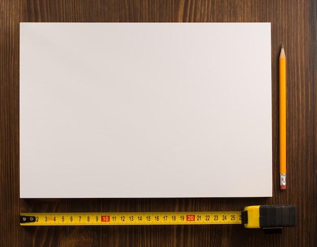 Taśma miernicza i ołówek na drewnianej teksturze