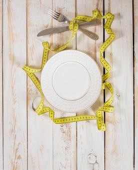Taśma miernicza na drewnianym tle. koncepcja diety