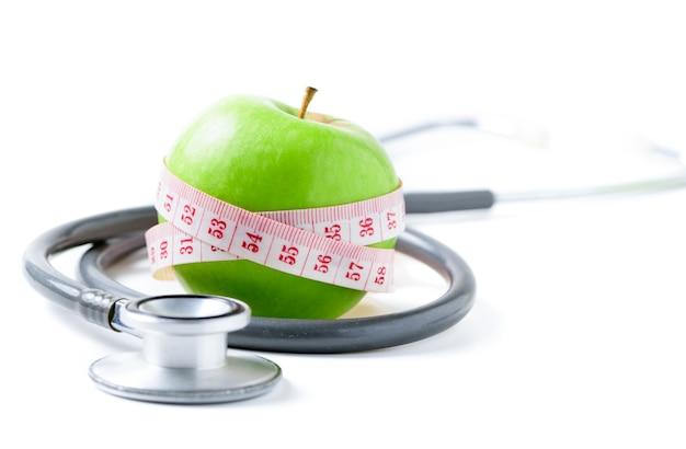 Taśma miernicza owinięta wokół zielonego jabłka ze stetoskopem na białym tle, koncepcja celu odchudzania, cel diety