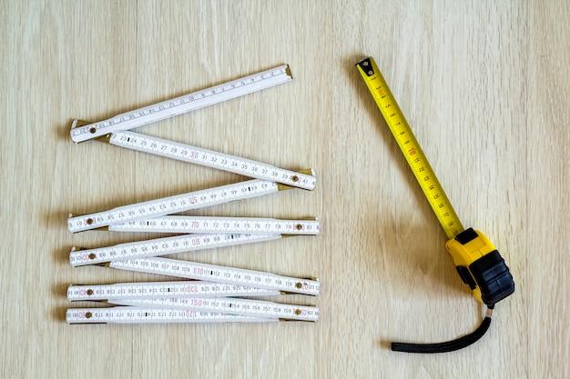 Taśma pomiarowa i metr na drewnie