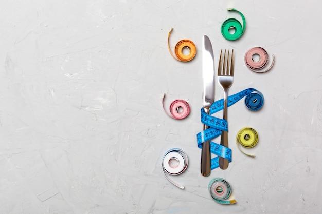 Taśmy pomiarowe, widelec i nóż koncepcja nadwagi