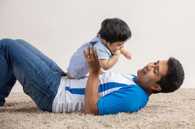 Tata bawi się na podłodze ze swoim synem w dzień ojca