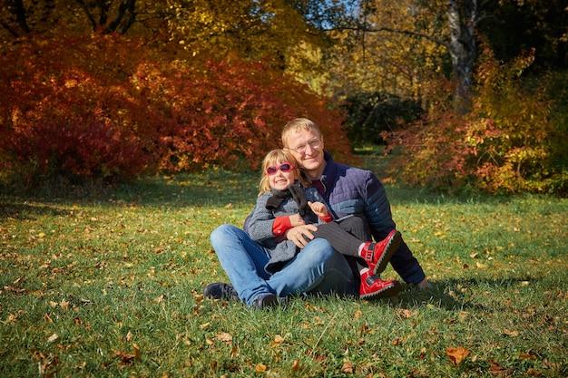 Tata bawi się z córką w jesiennym parku