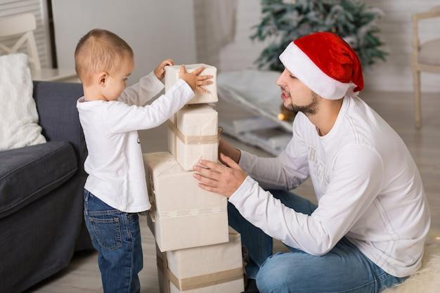 Tata bawi się ze swoim małym synkiem. spędzajcie razem czas podczas świąt bożego narodzenia.
