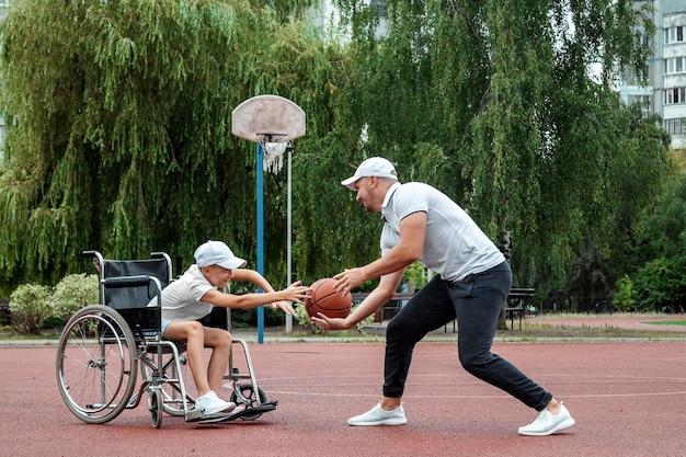 Tata bawi się ze swoim niepełnosprawnym synem na boisku sportowym. koncepcja wózek inwalidzki, osoba niepełnosprawna, satysfakcjonujące życie, ojciec i syn, aktywność, radość, koszykówka.