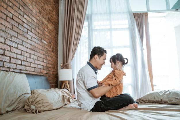 Tata bawi się ze swoją małą córeczką, siedząc na łóżku