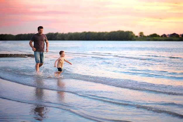 Tata biegnie za synem wzdłuż brzegu rzeki o zachodzie słońca.