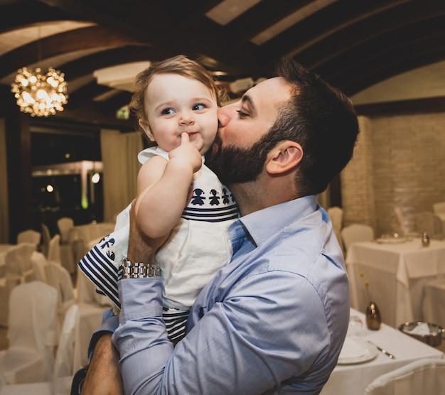 Tata całuje córkę.