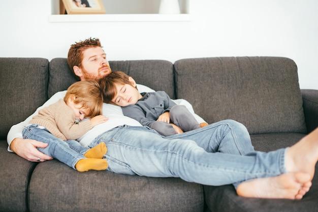Tata drzemie z synami na kanapie