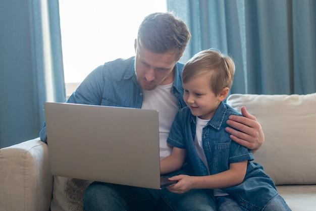 Tata dzień ojca i syna, patrząc na laptopa