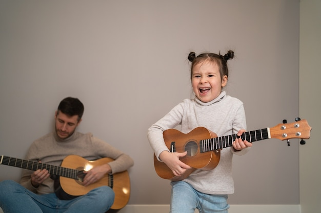 Tata gra na gitarze z córką. dziecko uczy się gry na instrumencie muzycznym z nauczycielem. muzyczny duet ojca z dzieckiem.
