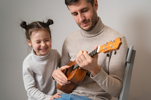 Tata gra na gitarze z córką.