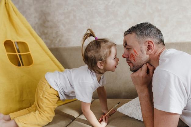 Tata i córeczka bawią się razem w domu na kanapie, uważnie się oglądając