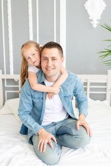 Tata i córka bawią się bawiąc się lub wygłupiając w domu na łóżku, szczęśliwa rodzina