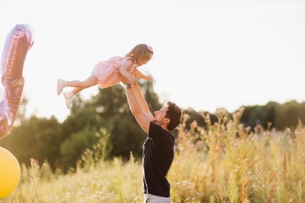 Tata i córka chodzą po ulicy o zachodzie słońca. tata rzuca córkę w ramiona