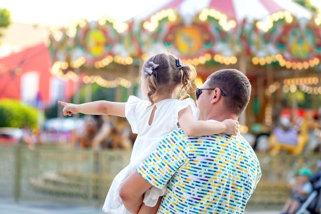 Tata i córka dziewczyna w parku rozrywki latem na wakacjach kazali spędzić czas, dziecko wskazuje palcem, widok z tyłu