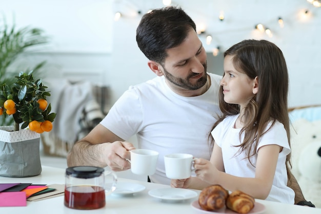 Tata i córka jedzą śniadanie w kuchni