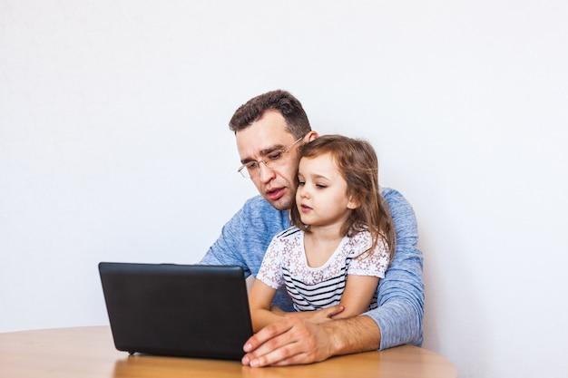 Tata i córka komunikują się z rodziną przez internet