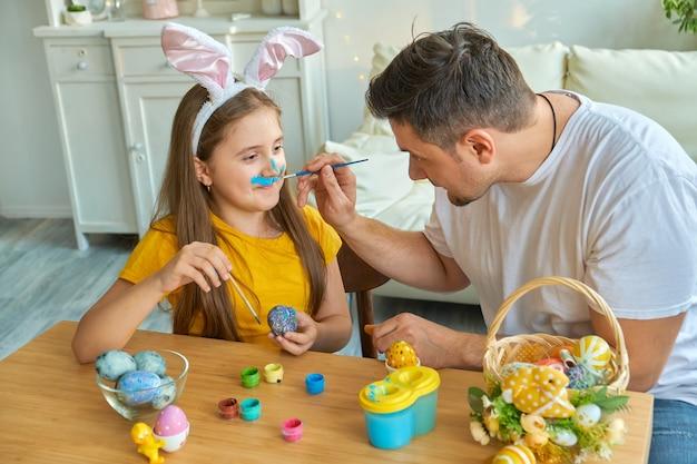 Tata i córka malują sobie twarze niebieską farbą do malowania jajek. na stole koszyk z pisankami i farbkami.