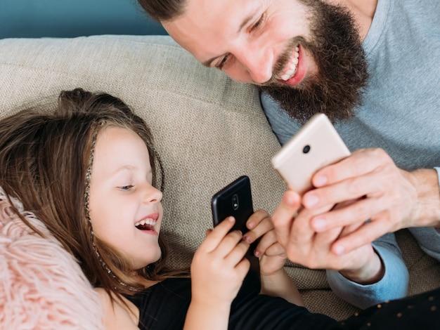 Tata i córka śmieją się razem po obejrzeniu zabawnego zdjęcia lub filmu w internecie. ojciec i dziecko za pomocą telefonu komórkowego.