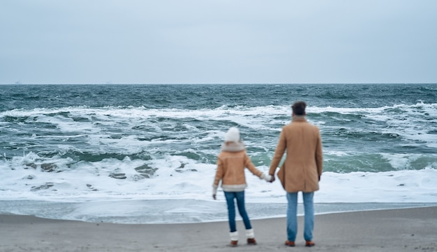 Tata i córka trzymają się za ręce patrząc na morze, ciesząc się szumem fal na plaży zimą.
