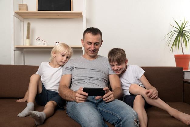Tata i dwaj synowie siedzą na kanapie i oglądają wideo przez telefon. wypoczynek rodzinny.