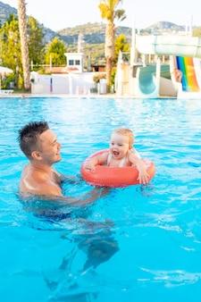 Tata i dziecko w dmuchanym kręgu w basenie ze zjeżdżalniami latem bawią się pływając, relaksując się i spędzając czas z rodziną