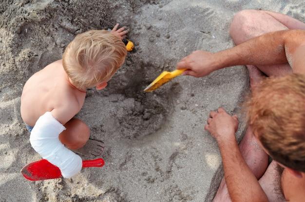 Tata i dziecko z gipsem na dłoni bawiące się w piaskach na plaży nad morzem