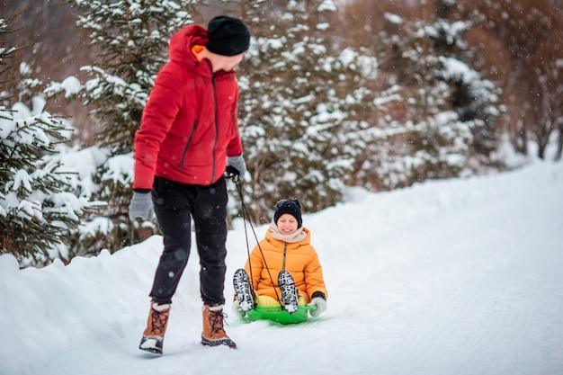 Tata i dziecko z saniami na śniegu