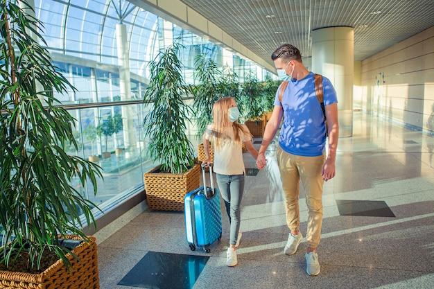 Tata i dziewczynka w maskach medycznych na lotnisku. ochrona przed koronawirusem i grippem