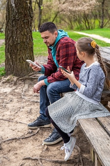 Tata i jego córeczka z telefonami w rękach nie zwracają na siebie uwagi.
