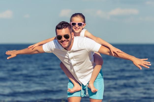 Tata i jego córka rozkładają ręce naśladując lot.