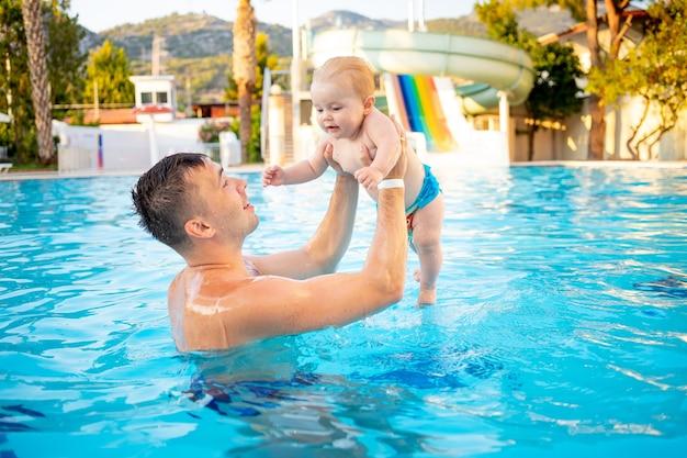 Tata i maluszek w basenie ze zjeżdżalniami latem dobrze się bawią pływając, relaksując się i spędzając czas z rodziną na wakacjach, wyrzucając dziecko w górę