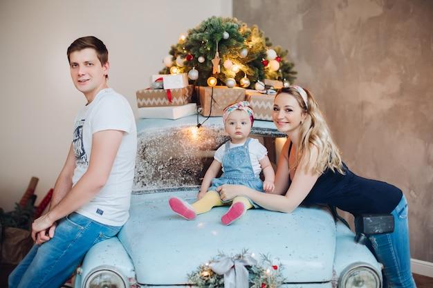 Tata i mama całują małą córeczkę z boku, pozując w wystroju do świątecznego pokoju.