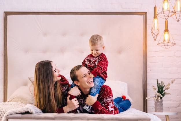 Tata i mama leżą na łóżku, a syn tata bawi się z nim. czas świąt.
