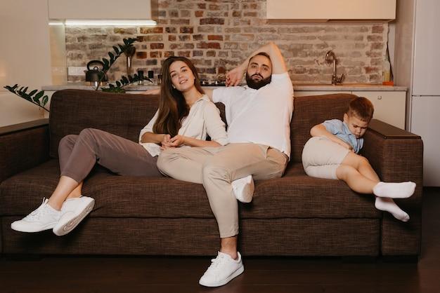 Tata i mama oglądają telewizję na kanapie, podczas gdy syn wieczorem śpi obok. rodzina w domu.