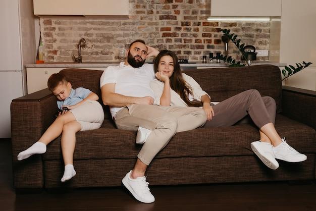 Tata i mama oglądają wieczorem telewizję na kanapie. syn gra na telefonie komórkowym w pobliżu swojej rodziny. krewni w domu.