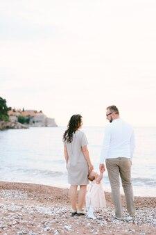 Tata i mama trzymają się za ręce dziewczynki stojącej na plaży w pobliżu willi milocer przeciwko
