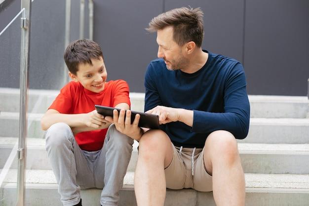Tata i syn bawią się dyskutując o nowej grze przy użyciu tabletu, siedząc na betonowych schodach w mieście