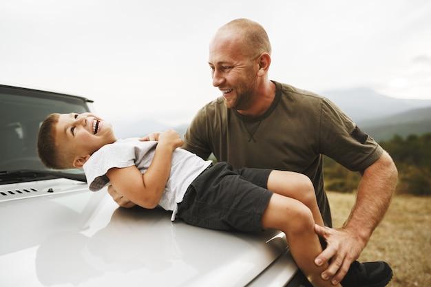 Tata i syn bawią się na masce samochodu w podróży
