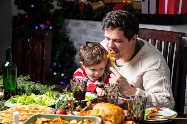Tata i syn bawią się przy stole podczas świątecznej kolacji