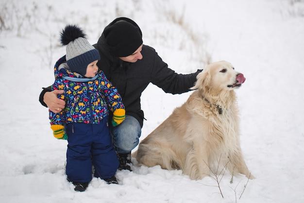 Tata i syn bawią się z psem na śniegu. golden retriever