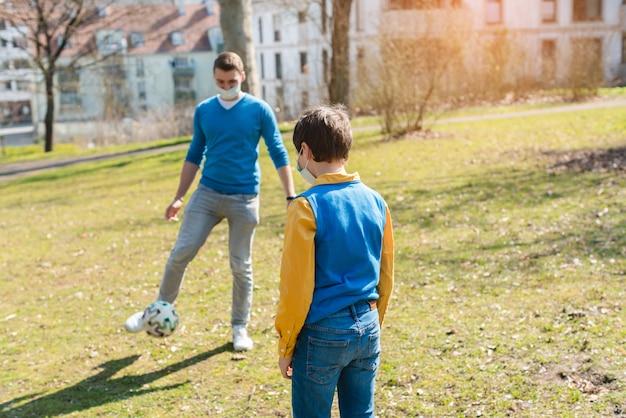 Tata i syn bawić się piłkę nożną w parku podczas kryzysu koronawirusowego
