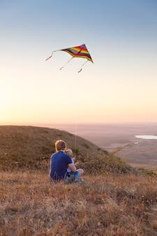 Tata i syn chłopca malucha puszczają latawiec o zachodzie słońca.