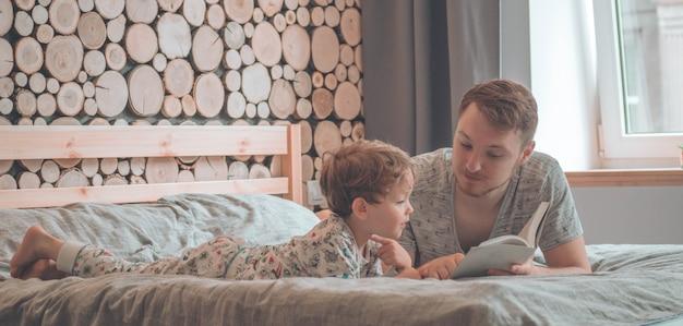 Tata i syn czytają razem książkę, uśmiechają się i przytulają